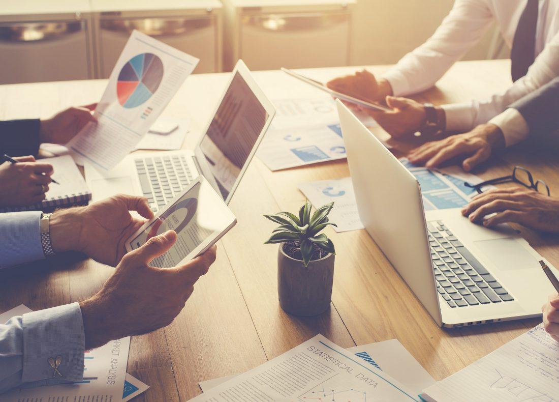 Groupe de personnes travaillant sur ordinateur et tablette autour d'un bureau
