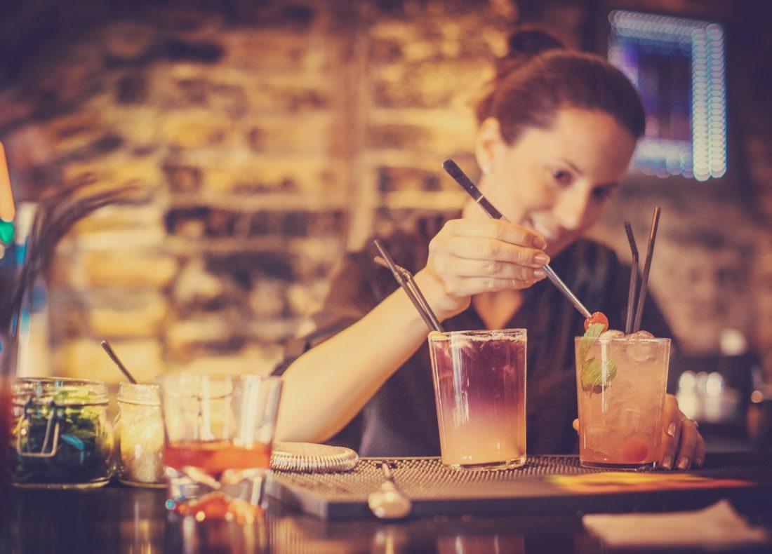 Portrait d'une barmaid préparant un cocktail au bar de l'hôtel Suitcase Hospitality