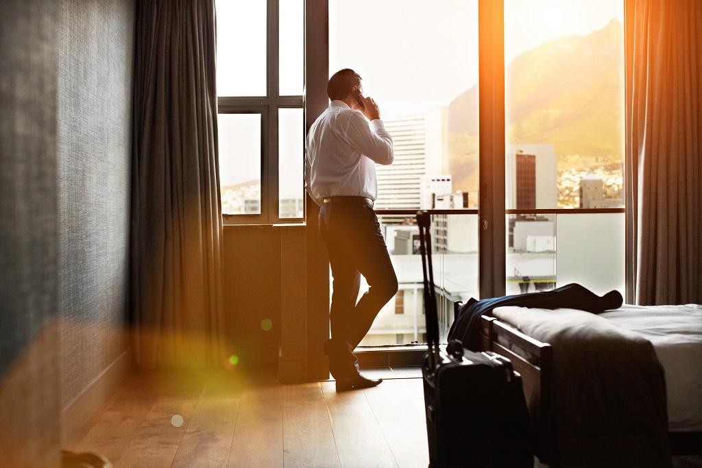 Homme d'affaires parlant au téléphone depuis la fenêtre de sa chambre d'hôtel