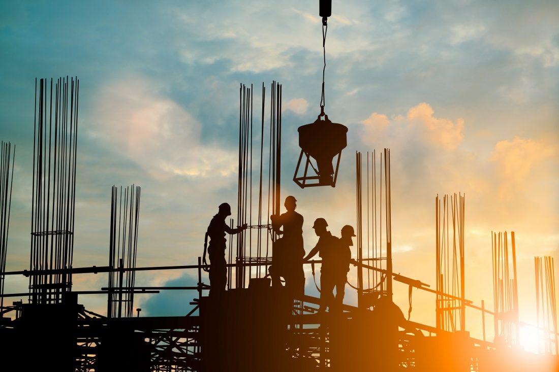 Silhouettes d'ingénieur et d'une équipe de construction sur un échafaudage en haut d'un projet immobilier