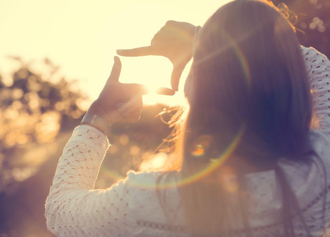 Femme vue de dos cadrant et visant l'horizon à l'aide de ses deux mains