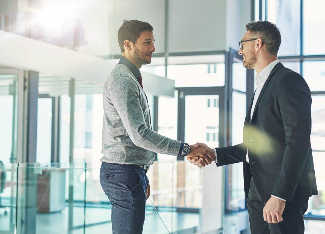 Deux hommes d'affaires se serrant la main à l'entrée d'un bureau