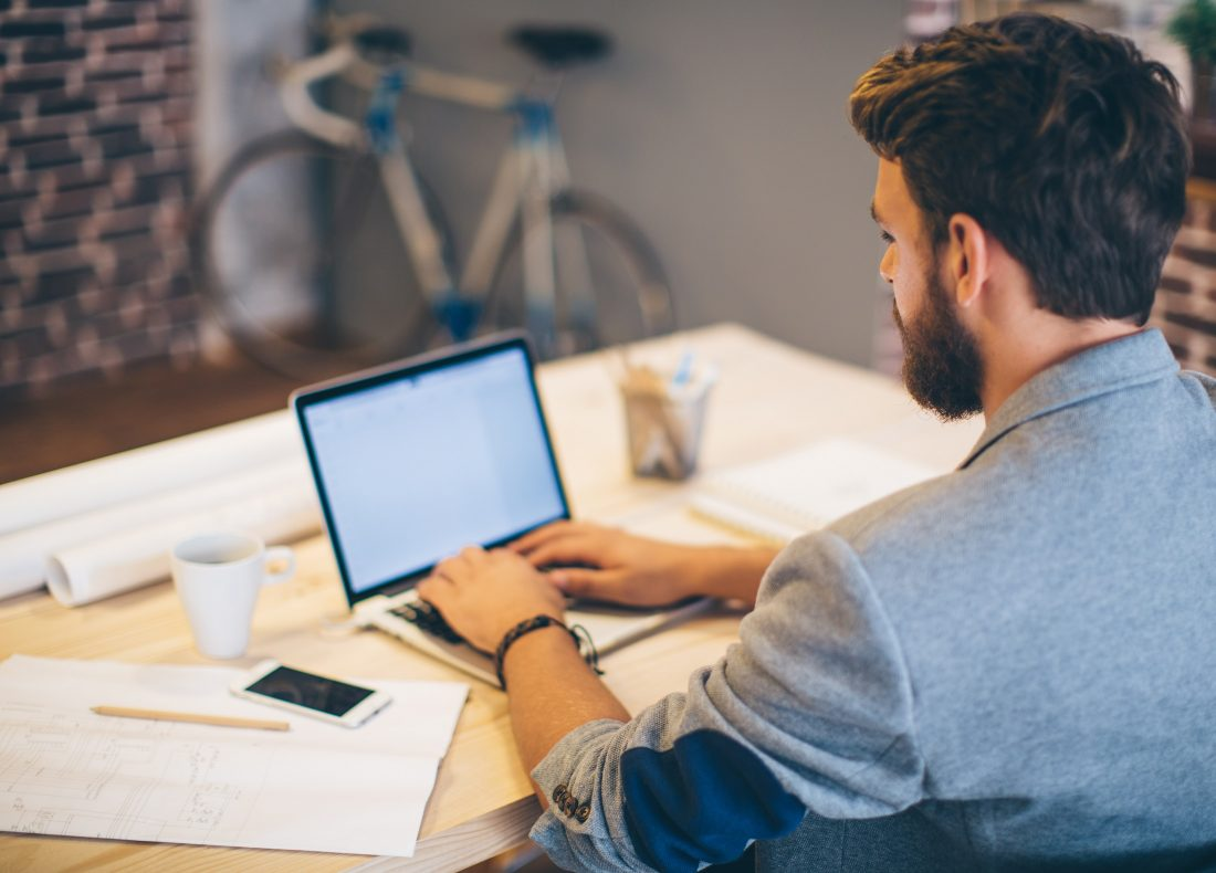 Homme postulant à une offre d'emploi depuis son ordinateur portable