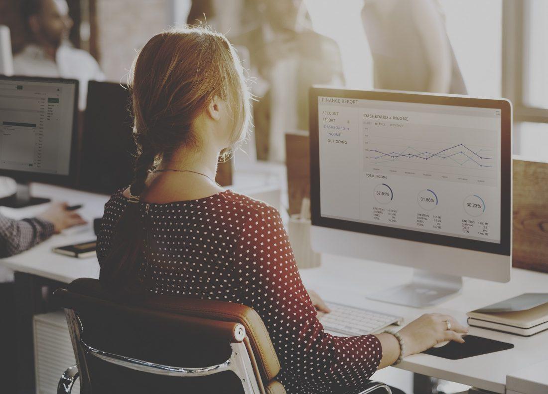 Jeune femme vue de dos analysant les performances de résultats