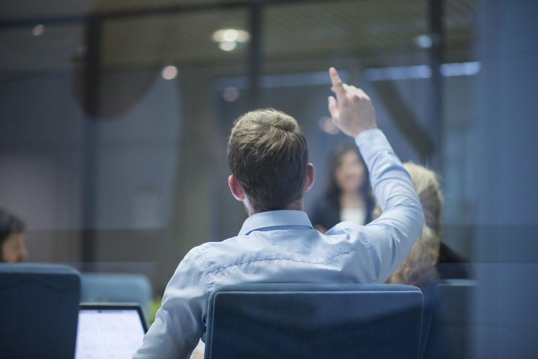 Homme d'affaires en réunion levant la main pour poser une question